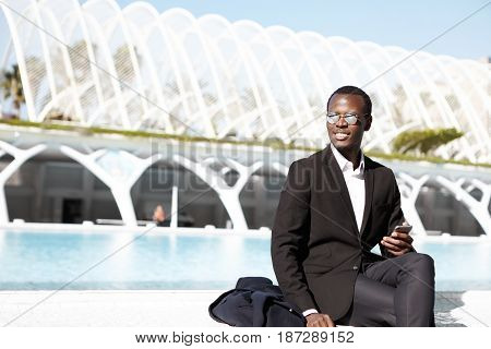 Happy Afro American Employee Wearing Black Formal Suit Having Broad Smile Sitting Outdoor Holding Mo