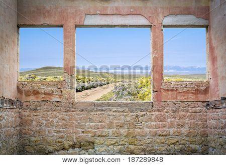 ranch road through mountain valley as seen through windows of an abandoned house