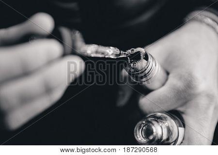 guy digs in the fill up e-cigarette. Vape, vaping