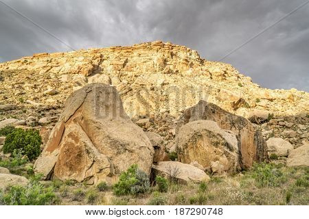 Book Cliffs under stormy clouds - desert landscape of eastern Utah with a cliffs and boulders