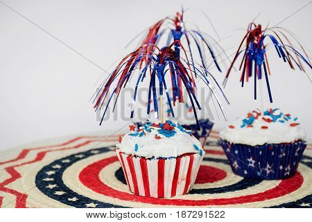patriotic cupcakes with candy sprinkles and party sparkler decoration