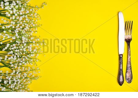 Iron vintage cutlery on a yellow background and a bouquet of white lilies of the valley top view empty space in the middle