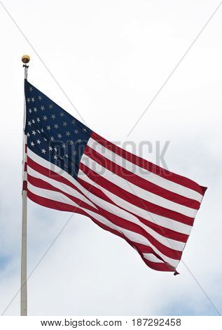 American flag waiving on a wind outside on a cloudy day