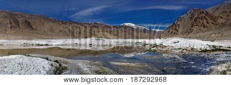 Mountain Salt Lake: To The Fore Blue Water With A Mirror Image Of The Mountain And Peel Of Rock Salt