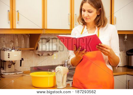 Mature housewife cook chef holding reading cookbook looking for recipe. Middle aged woman preparing food in kitchen.
