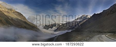 Early foggy morning on Leh Manali Highway: the road passes in clouds among the highest mountains the slopes are lit by the sun the summer Ladakh Northern India.