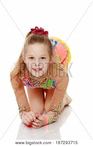 Beautiful little girl gymnast posing in front of the camera doing exercise on the floor.Isolated on white background.