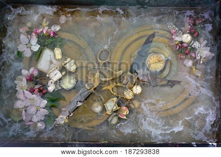 Original art still life: two pair of scissors grappled with handles and lie on a round brass plate among the flowers of an apple tree and flakes of paint floating on the surface of the water.