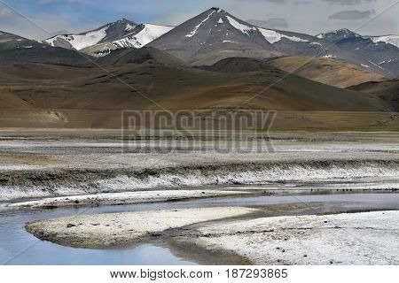 The mountain river flowing along the salt desert among the high Tibetan hills the white banks of salt look like snow Northern India.
