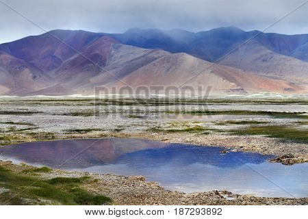 Thunderstorm at the high mountains of the Tso Kara lake: lilac clouds descend to the mountains the calm surface of the lake reflects the sky and hills soft colors of greens on the banks India.