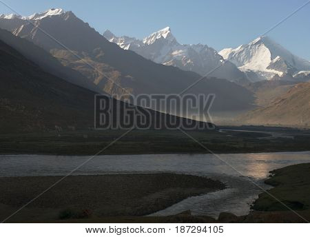 Sunrise in the high mountains of the river valley: in the foreground in the shadow of a stream of water the surface is reflected by the sun background high peaks under the blue sky Zanskar India.