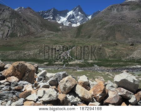 Hanging glacial valley in Zanskar: in the foreground there are many moraine boulders behind a deep desert valley and high snow peaks with glacier Northern India.