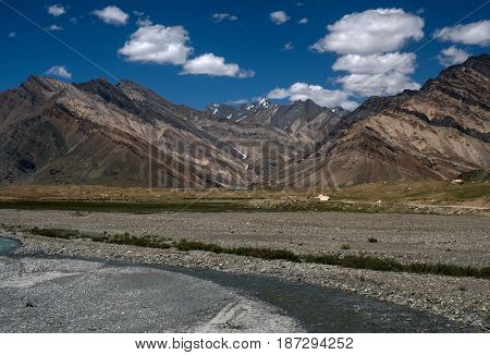 High striped brown mountains the valley of the river in the foreground arc the aquamarine pure water Zanskar Tibet India.