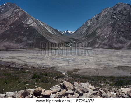 Wide moraine valley in Zanskar: a large stream flows along the riverbed intertwined in the background glacier peaks in front of boulders and grass on the Tibet the Himalayas.
