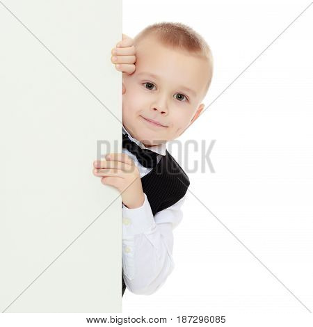 Beautiful little boy in a strict black suit , white shirt and tie.Boy peeping over white banner.Isolated on white background.