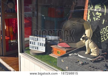 front shop window of anonymous record music shop with sign fresh wax from japan vinyl record player and dog statue
