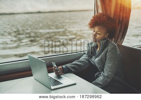 Meditative young black freelancer girl is chilling in ship cabin with laptop on table and smartphone in her arm curly afro american female waiting for internet connection while travelling on ship