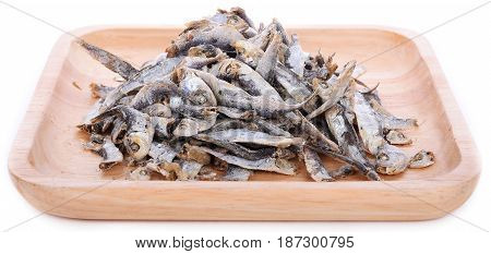 Dried sardine on wooden plate isolated in white background