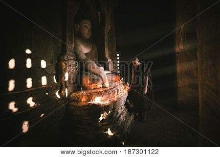 Novices praying with candles in front of buddha statue inside old pagoda Bagan Myanmar