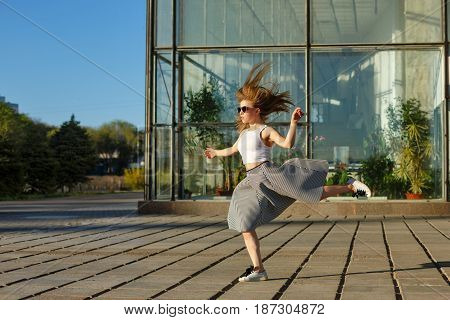 Young attractive hipster girl running. Hair fluttering. She is dressed in a top sunglasses skirt and sneakers. Girl dancer.