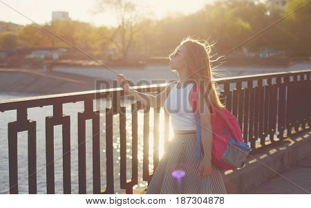 Young attractive hipster girl admiring the sunset. She is dressed in sunglasses top and skirt. She has a backpack.