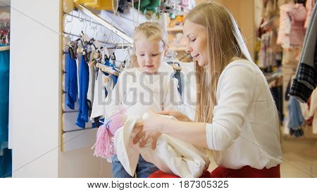A young mother wraps a new doll for her little daughter in a children's store
