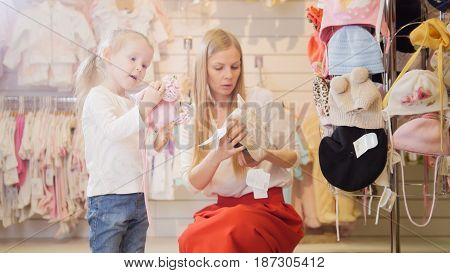 Mother and daughter consider baby beanieA young mother with a small daughter to consider beanie in the children's clothing store