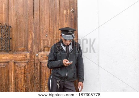 Police officer in Guatemala looking at his cell phone. Taken January 5 2016 in Antigua Guatemala.