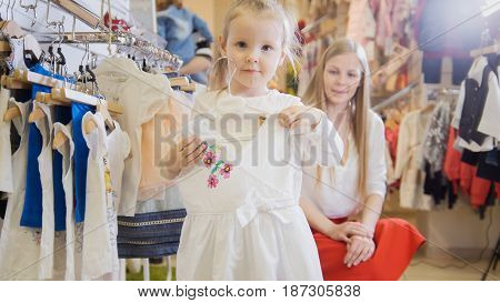 ute little girl with a white light summer dress in the hands of the children's clothing store