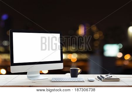 desktop computer on work table and city night background