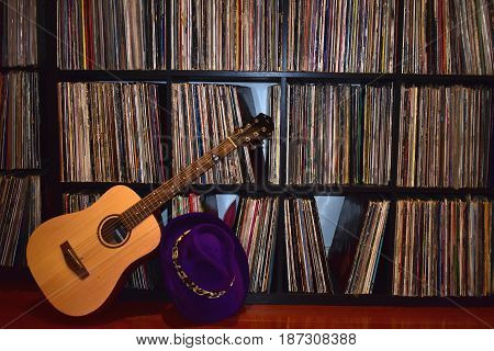 bookcase of vintage music vinyl records in background with guitar and royal purple felt hat in foreground