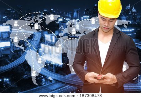 smart construction manager with walkie-talkie or two way radio in hand and yellow safety helmet with world map network connection on blurred night city background industrial technology concept.;