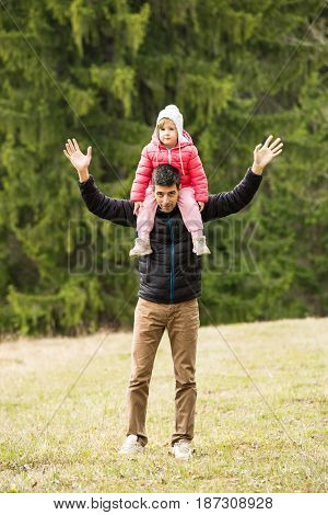 Happy father and daughter walking in nature at mountain
