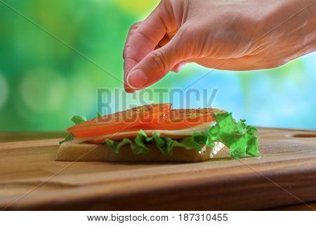 Girl's hand salts sandwich outdoors, on wooden board