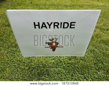 white hayride sign with bird in green grass