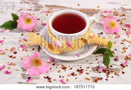 Cup Of Hot Tea With Wild Rose Flower On Rustic Wooden Background