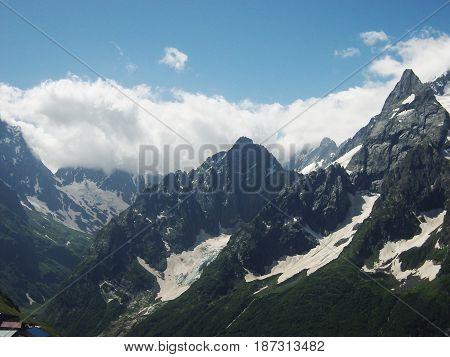 Snowy mountains and blue sky with clouds. Caucasus mountains.