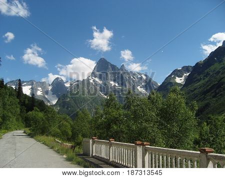 Snowy mountains and blue sky with clouds. Road in a Caucasus mountains.