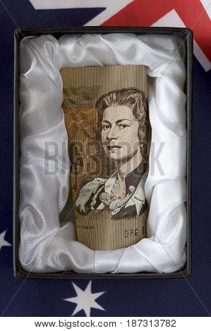 Discontinued Australia one dollar note in a coffin with Australian flag.