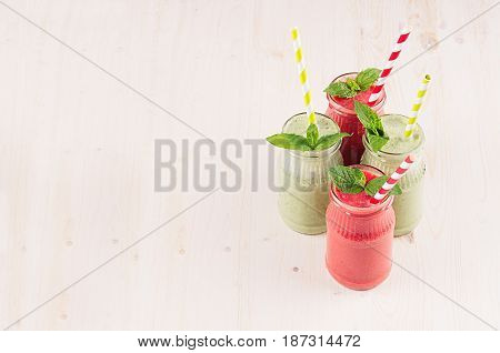 Freshly blended green and red fruit smoothie in glass jars with straw mint leafs of strawberry and apples. White wooden board background copy space.
