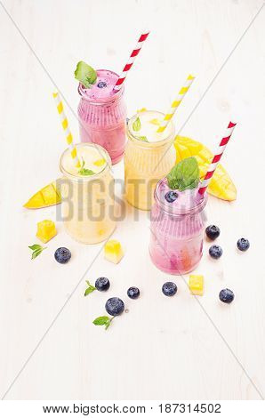 Yellow and violet fruit smoothie in glass jars with straw mint leaves mango slices berry. Soft white wooden board background.