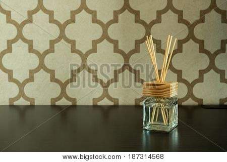 Aroma Glass Bottle And Perfume Stick On Pattern Wall Background