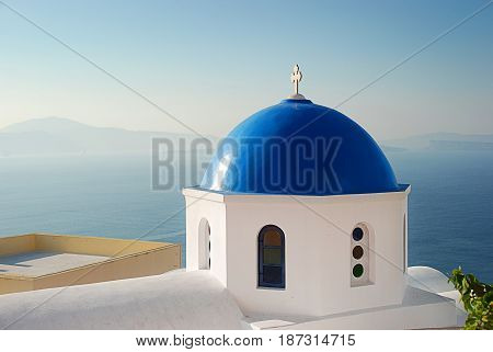 Iconic blue domed church of Santorini Greece overlooking the caldera