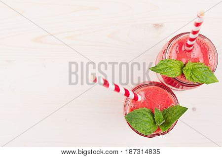Freshly blended red strawberry fruit smoothie in glass jars with straw mint leaf top view. White wooden board background copy space.