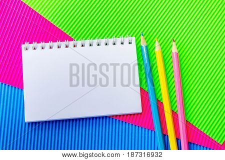 Blank  spiral notepad and colorful pencils on green, pink and blue corrugated cardboard paper . Space for text or message
