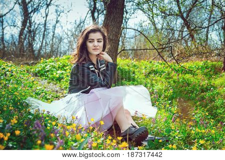 Beautiful teen girl wearing black leather jacket and pink tutu tulle skirt sitting on spring meadow with yellow and purple flowers in the forest