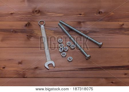 Several nuts bolts and a wrench on a wooden table.