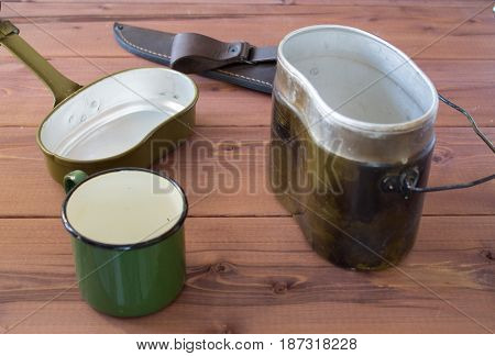 Camping dishes on a wooden background. Cup knife on a table. Camping set.