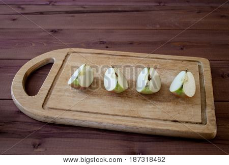 Cut apples with a kitchen knife on a cutting board. Wooden table.