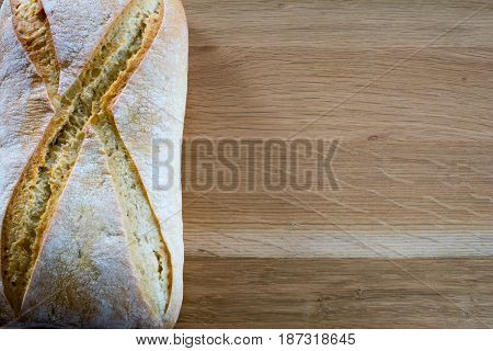 Fresh loaf of bread on wooden oak table top. Space for text.